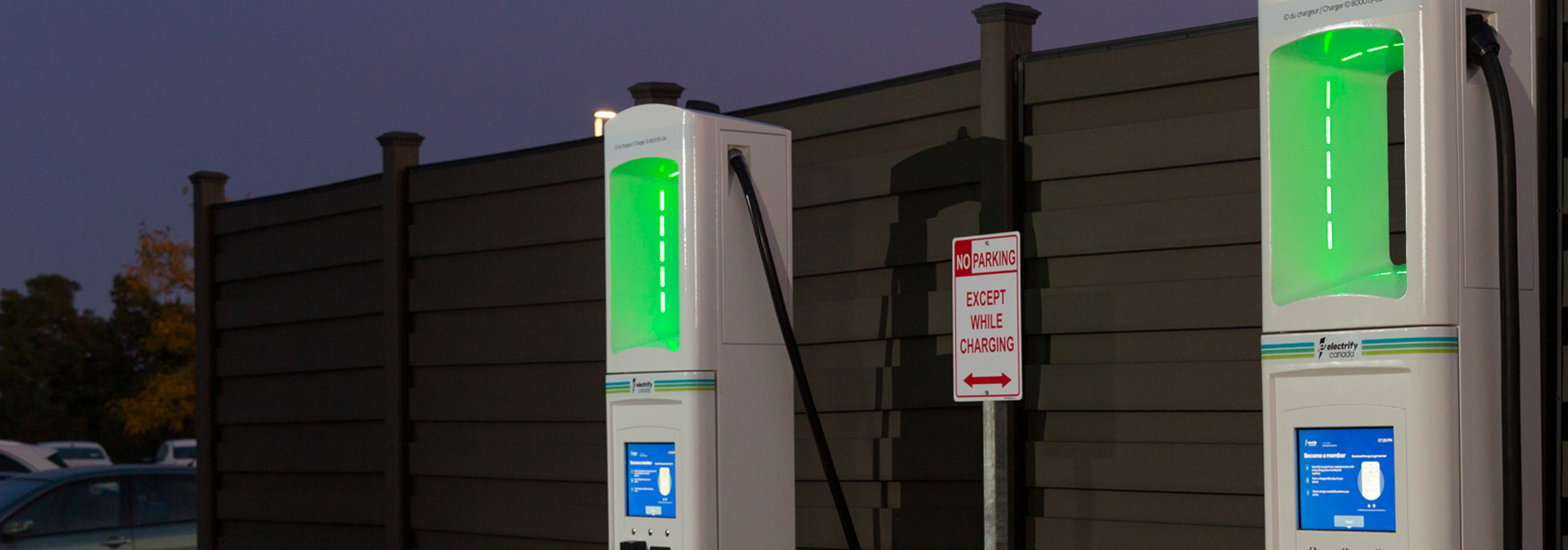 Two Electrify America charging stations glowing green at night